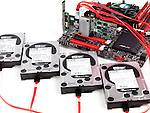 Closeup of four hard drives connected to computer motherboard with a RAID controller