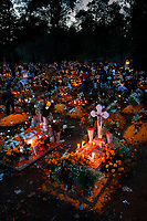 Mexican families gather at the cemetery, lighting candles and bringing flowers, to honor their deceased relatives during the Day of the Dead festivities in Tzurumútaro, Michoacán, Mexico, 3 November 2014. Day of the Dead ('Día de Muertos') is a syncretic religious holiday, celebrated throughout Mexico, combining the death veneration rituals of the ancient Aztec culture with the Catholic practice. Based on the belief that the souls of the departed may come back to this world on that day, people gather on the gravesites praying, drinking and playing music, to joyfully remember friends or family members who have died and to support their souls on the spiritual journey.