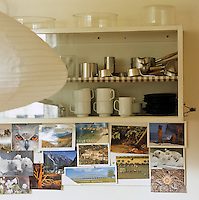 A collection of postcards are on display below a glass-fronted cupboard filled with cups and saucers and small pots and pans