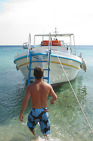 Man in board shorts walking towards a small Greek boat in Mykonos, Greece