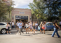 Hordes of millennials pour out of the Morgan Avenue subway station in the Bushwick neighborhood of Brooklyn to take in the experiential 29 Rooms installation on Sunday, September 11, 2016. The exhibit by the women's lifestyle website Refinery29 is a social media spectacle with art and culture themed rooms designed with selfies in mind. The installation was wildly popular, in part due to the social media aspect, so popular that the line was cut off at noon, hours before the last entry. (© Richard B. Levine)