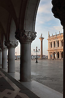 Arcade of the Doge's Palace or Palazzo Ducale, begun 1340 and built in Venetian Gothic style, on the Piazzetta San Marco, Venice, Italy. The palace has 2 arcades with 14th and 15th century capitals and sculptures, and a loggia above with a decorative brickwork facade. It was the residence of the Doge of Venice, the supreme authority of the former Republic of Venice, until the Napoleonic occupation in 1797, and is now a museum. On the right is the Colonna de San Todaro, with a statue of the Byzantine saint San Teodoro Amasea, 12th century, by Nicolo Barattieri, and the corner of the Biblioteca Nazionale Marciana, or National Library of St Mark's, built in Renaissance style in 1537-53 by Jacopo Sansovino, then extended by Vincenzo Scamozzi in 1588. The city of Venice is an archipelago of 117 small islands separated by canals and linked by bridges, in the Venetian Lagoon. The historical centre of Venice is listed as a UNESCO World Heritage Site. Picture by Manuel Cohen