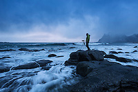 Photographer Stands on rock surrounded by waves at Uttakleiv beach, Vestvågøy, Lofoten Islands, Norway