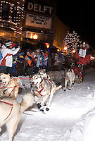 Crowds cheer as a sled dog team mushes through historic downtown Marquette, Mich. during the U.P. 200 Sled Dog Championship.