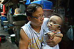 Iluminada Castillo holds her 3-year old grandson Ceyrus outside his home in the Malate neighbohood of Manila. She is a member of Kaisahan ng Magulang at Anak na Maykapansanan (Kaisaka), a mothers' group that carries out community based rehabilitation with families which have members with disabilities.