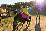 Old Bethpage, New York, U.S. 29th September 2013. A father takes a photo of his daughter riding a pony as closing time arrives at The Long Island Fair. A yearly event since 1842, the county fair is now held at a reconstructed fairground at Old Bethpage Village Restoration.