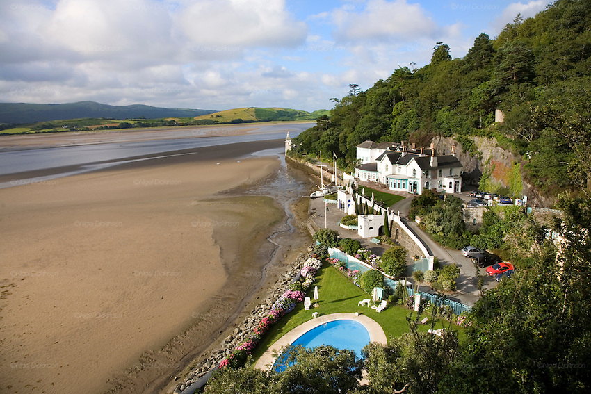 "Portmeirion, in North Wales, is a resort, where no one has ever lived. A self-taught Welsh architect named Sir Clough Williams-Ellis built it out of architectural salvage between the 1920s and 1970s, loosely based on his memories of trips to Portofino. Including a pagoda-shaped Chinoiserie gazebo, some Gothic obelisks, eucalyptus groves, a crenellated castle, a Mediterranean bell tower, a Jacobean town hall, and an Art Deco cylindrical watchtower. He kept improving Portmeirion until his death in 1978, age 94. It faces an estuary where at low tide one can walk across the sands and look out to sea. At high tide, the sea is lapping onto the shores. Every building in the village is either a shop, restaurant, hotel or self-catering accomodation. The village is booked out at high season, with numerous wedding receptions at the weekends. Very popular amongst the English and Welsh holidaymakers. Many who return to the same abode season after season. Hundreds of tourists visit every day, walking around the ornamental gardens, cobblestone paths, and shopping, eating ice-creams, or walking along the woodland and coastal paths, amongst a colourful assortment of hydrangea, rhododendrons, tree ferns and redwoods. The resort boasts two high class hotels, a la carte menus, a swimming pool, a lifesize concrete boat, topiary, pools and wishing wells. The creator describes the resort as ""a home for fallen buildings,"" and its ragged skyline and playful narrow passageways which were meant to provide ""more fun for more people."" It does just that.///Portmeirion Hotel overlooking the estuary Afon Dwyryd towards Porthmadog and Tremadog."