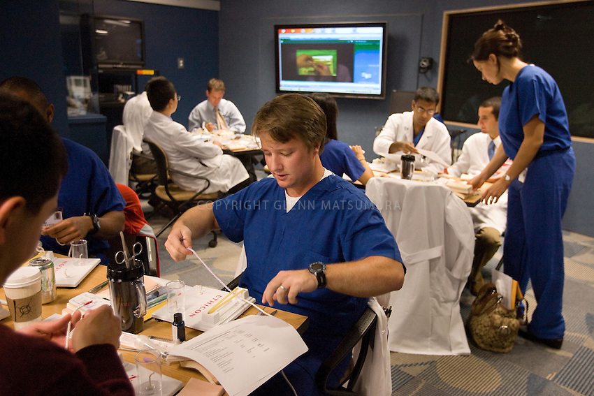 "Stanford Goodman Simulation lab ""boot camp"" at Stanford Hospital. First year residents practice suturing on tissue pads. Owen Palmer practices tieing knots.  Mary-Anne Purtill, MD leads class. Other instructor: Catherine Mohr, MD (black top/slacks). Program director: Sandra Feaster, RN."