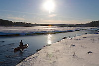 A solo canoeist paddles a red canoe on the Dead River in winter near Marquette Michigan.