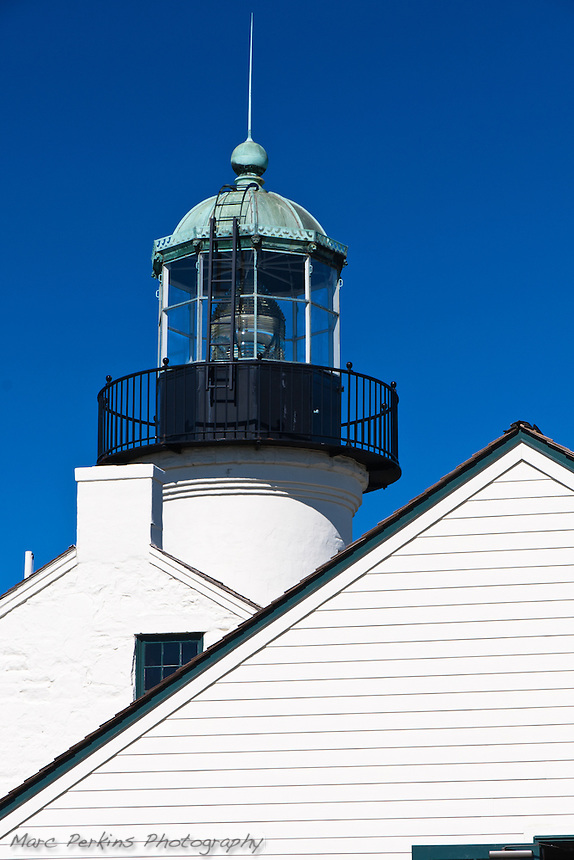 Old Point Loma Light is in Cabrillo National Monument near San Diego, CA.  This image is made from just south of the assistant keeper's house, showing the points of both the roofs of that building and the main lighthouse with its chimney.  Behind these, standing tall, is the lantern room of the lighthouse, with its installed lens.  The bright white buildings contrast with the clear blue sky and black lantern room.