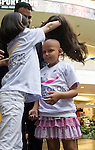 Isabela Osorio (R) a patient with cancer tests her new wig during a donation ceremony as a commitment to actively fight against cancer in Medellin, Colombia, May 25, 2012.  Colombia celebrated on 31 January, 7, 14 and 21 February some days of donating hair in Beauty Centres Fundayama ALQVIMIA and foundation (Foundation for support and support people with breast cancer), it received 300 donations of hair with which they made 200 wigs  Photo by Fredy Amariles/View