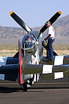 A crewmember stands on the wing of the Unlimited Air Racer &quot;Speedball Alice&quot; assisting the pilot to prepare for a heat race during the Reno National Championship Air Races.