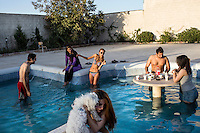 A group of young men and women eat and mess about in  a swimming pool.