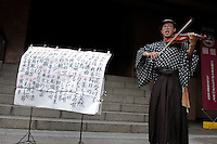 A man in traditional costume playing a violin and singing classic Enka songs in the grounds of Toganji Temple in Sugamo, Tokyo, Japan. September 7th 2008