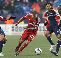 Toronto FC forward Jeremy Brockie (22) dribbles in a crowd. In a Major League Soccer (MLS) match, the New England Revolution (blue) defeated Toronto FC (red), 2-0, at Gillette Stadium on May 25, 2013.