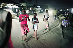 KINSHASA, DEMOCRATIC REPUBLIC OF CONGO - APRIL 29: Esther Yandakwa (c), age 9, walk the streets looking for customers with her friends on April 29, 2006 in Matonge district in central Kinshasa, Congo, DRC. Esther is homeless and works a prostitute together with four fourteen-year-old friends. They live outside next, to a polluted river. She's been living on the streets for three years, and has run away from her family. She has from time to time been living in a homeless shelter but doesn?t like the rules there. She usually smokes cigarettes, marijuana, drinks whiskey and sometimes takes Valium. She charges the clients as little as US$ 1. About 15,000 children are estimated to live on the streets of Kinshasa. Congo, DRC is in ruins after forty years of mismanagement by the corrupt dictator and former president Mobuto Sese Seko. He fled the country in 1997 and a civil war started. The country is planning to hold general elections by July 2006, the first democratic elections in forty years. (Photo by Per-Anders Pettersson)