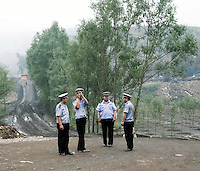 Security officers assess a coal mining site in Shanxi Province.
