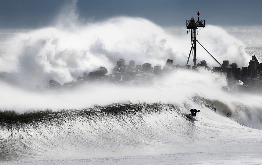 "MANASQUAN, NJ (Dec. 21, 2012) — An unidentified surfer rides a 12-foot wave as an even bigger set explodes over the south jetty of Manasquan Inlet during an epic post-Hurricane Sandy winter surf session now referred to as the ""Doomsday Swell"""