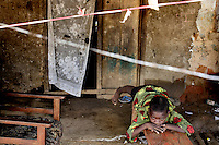 Nine year old Idris Conthe, whose mother recently died from ebola, lies on a bench in his family home which is under quarantine along with 46 households on the main street of Grafton after at least 17 cases of ebola were reported in the area. Officially no one is allowed to enter or leave the houses, but in reality the quarantine is far from strict and villagers can easily leave their houses through their backdoors.