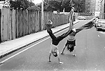 Teenage girls playing turning cartwheels in Oswin street SE11 Elephant and Castle, South London UK 1975.In the background is Rowton House, which later became The London Park Hotel.