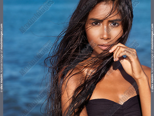 Beautiful young woman expressive portrait with long wet dark hair against blue sea water