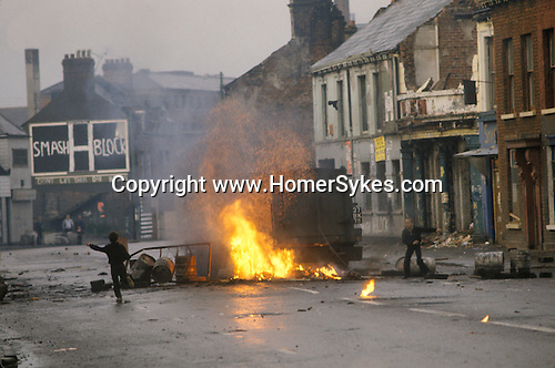 Northern Ireland The Troubles. 1980s. An armoured British army vehicle drives through road barricade  the Falls Road, kids throwing stones and pretending to be older than they are.