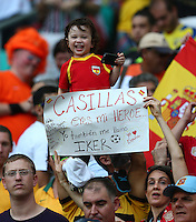 A young Spanish fan is waved in the air by his father