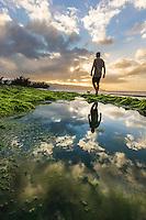 A man walks with his dog along a rocky seashore at sunset, Pua'ena Point, North Shore, O'ahu.