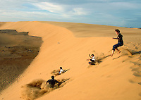 Tourists play in sand dunes outside the coastal town of Coro.
