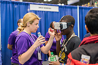 A worker from Comcast NBCUniversal assists a visitor with a Samsung Gear VR Virtual reality device at a Career Expo held at the FIRST Robotics NYC Championship at the Jacob Javits Convention Center in New York on Sunday, March 13, 2016. The expo enables participants to speak with companies and professional organizations giving a real-world look into science and technology as used in the business world and their career opportunities. (© Richard B. Levine)