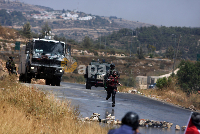 A Palestinian woman waves a Palestinian flag in front of a truck spraying foul smelling water during clashes with Israeli soldiers at a weekly protest against a nearby Jewish settlement, in the West Bank village of Nabi Saleh, near Ramallah July 6, 2012. Photo by Issam Rimawi