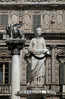 """Fountain of Madonna Verona, 4th century, and the lion of Saint Mark at the top of a 16th century marble column, in the background, Piazza delle Erbe, Verona, Italy. In the centre of the Piazza delle Erbe (Square of Herbs) is a fountain built in 1368, perhaps by Bonino da Campione with a 4th century Roman statue, known as the """"Madonna Verona"""". The winged lion is the symbol of Saint Mark, the patron saint of Venice, reminding the Veronese of their long period spent under Venetian dominion. Picture by Manuel Cohen."""