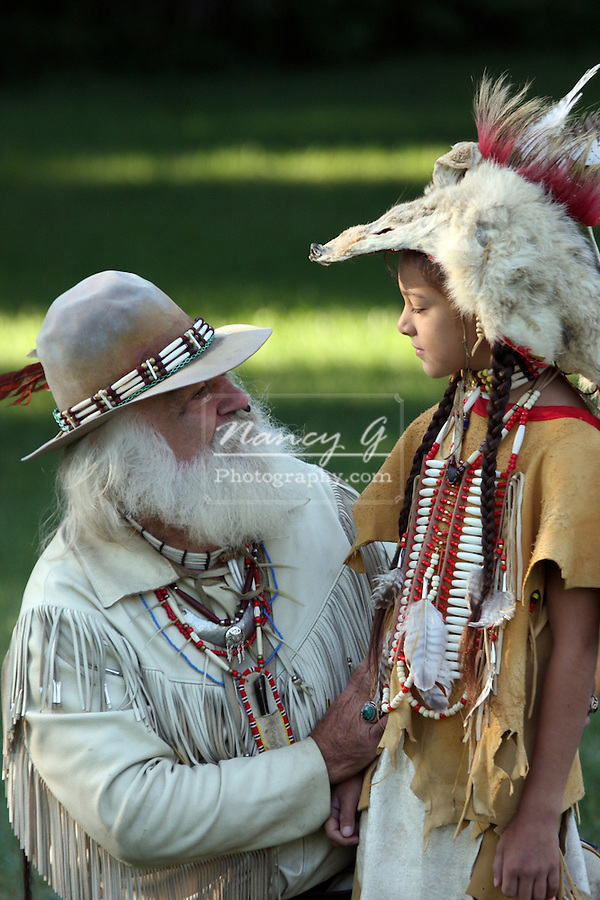 A young Native American Indian boy talking with a mountain man buckskinner