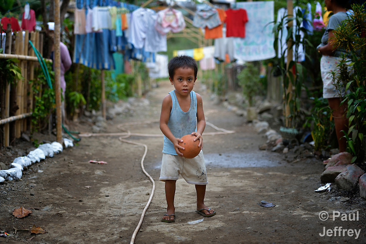 A boy plays with a ball in a narrow street in the Suburban neighborhood of Rodriguez, Rizal, in the Philippines. Most of the community's families were relocated here from other area of Manila and the nearby countryside to make way for urban renewal projects or to move them out of harm's way. Yet the new community was hit hard by Typhoon Ketsana in 2009, and Christian Aid, a member of the ACT Alliance, provided emergency relief supplies. Over the years since, with help from Christian Aid and other groups, community members have organized themselves and engaged in a process of disaster risk reduction, including identifying and mapping high-risk zones and evacuation routes in their area. Christian Aid has also assisted with financial and technical support for income generating livelihood projects and community enterprises.