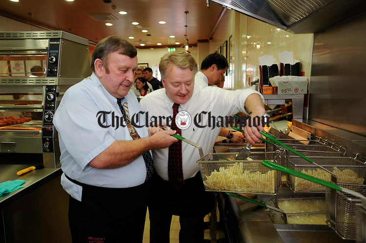 Mayor of Ennis Frankie Neylon gets frying with a little help from Franchisee Michael Grace at the oifficial opening of the new Hillbilly's fast food restaurant at O Connell Street, Ennis. Photograph by John Kelly.