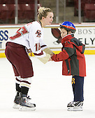Kelli Stack (BC - 16) skates with a young fan. - The Boston College Eagles women's team hosted a fan skate following their victory over Harvard on Sunday, December 5, 2010, at Conte Forum in Chestnut Hill, Massachusetts.