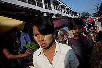 Women wearing tanaka face powder walk through a Rangoon (Yangon) market. Tanaka powder comes from a plant and is said have various health benefits for the skin.
