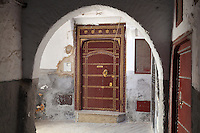 A decorative red door with gold studwork in a narrow street in the medina or old town, seen through an archway, Tetouan, on the slopes of Jbel Dersa in the Rif Mountains of Northern Morocco. Tetouan was of particular importance in the Islamic period from the 8th century, when it served as the main point of contact between Morocco and Andalusia. After the Reconquest, the town was rebuilt by Andalusian refugees who had been expelled by the Spanish. The medina of Tetouan dates to the 16th century and was declared a UNESCO World Heritage Site in 1997. Picture by Manuel Cohen