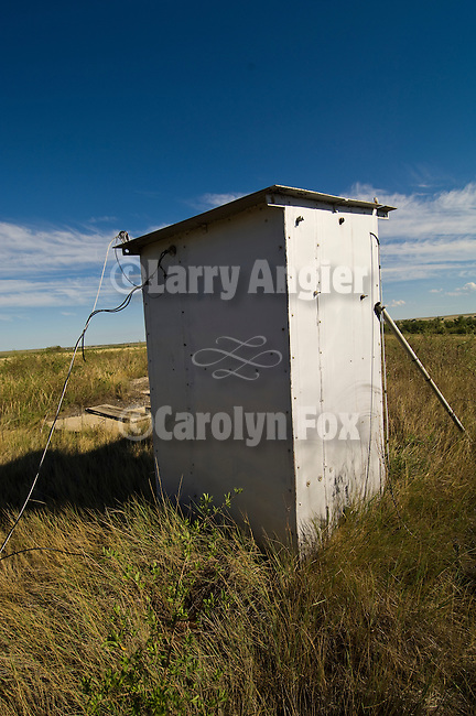 Hill-top white wooden outhouse wired down to the earth on the Great Plains of Colorado