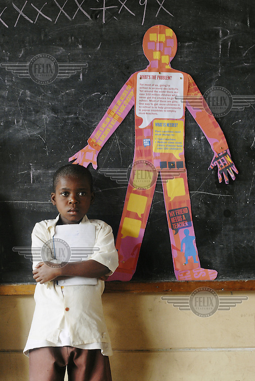 Student standing next to a blackboard in front of a poster for the 'Every child needs a teacher' campaign, which aims to urge political leaders to provide education for all children in developing countries..