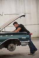 very good looking muscular auto mechanic with grease and dirt on his face leaning over a classic car in repair