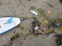 A surfboard lies on the sand  on the Legian beach, with seaweed full of plastic and other garbage. Enormous amounts of litter wash up every day, especially in the rainy season.