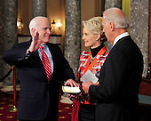 United States Senator John McCain (Republican of Arizona) raises his right hand during the photo-op of the reenactment of his swearing-in in the Old Senate Chamber in the U.S. Capitol in Washington, D.C. on Wednesday, January 5, 2011.  His wife, Cindy is at center and U.S. Vice President Joe Biden is at right..Credit: Ron Sachs / CNP.(RESTRICTION: NO New York or New Jersey Newspapers or newspapers within a 75 mile radius of New York City)