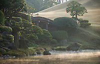 Mist rising from the water at sunrise over the ornamental lake of the Suizen-ji water garden