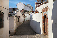 Narrow street with traditional houses in El Albayzin, the medieval Moorish old town of Granada, Andalusia, Spain. From the 8th to the 15th centuries, Granada was under muslim rule and retains a distinctive Moorish heritage. Granada was listed as a UNESCO World Heritage Site in 1984. Picture by Manuel Cohen