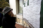 An unnamed woman looks through a list of names of people who have been delivered to a temporary morgue inside the Ishinomaki Municiple Gymnasium in Ishinomaki, Japan on 15 March, 2011.  Photographer: Robert Gilhooly