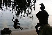 Children play on the beach, beside a fallen trunk of a coconut tree whose roots had been exposed by sea erosion of the land, on the shoreline of Han Island, Carterets Atoll, Papua New Guinea, on Monday, Dec. 11, 2006.  Rising sea levels have eroded much of the coastlines of the low lying Carteret islands (situated 80km from Bougainville island, in the South Pacific), and waves have crashed over the islands flooding and destroying what little crop gardens the islanders have. Food is in short supply, banana and swamp taro crops are failing due to the salt contamination of the land, and the islanders live on a meagre one meal per day diet of fish and coconut. There is talk by the Autonomous Region of Bougainville government to relocate the Carteret Islanders to Bougainville island, but this plan is stalled due to a lack of finances, resources, land and coordination.