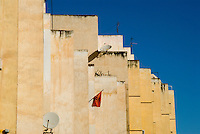 Tall yellow houses against the blue sky in the New Town, Fez, Morocco.