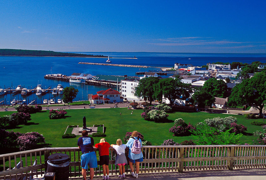 A FAMILY LOOKS OUT ON MACKINAC ISLAND FROM FORT MACKINAC ON MACKINAC ISLAND, MICHIGAN.