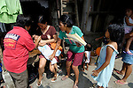Carmen Morano (left), a village health worker in Paltao, Philippines, applies vitamin drops to children in a poor community. Morano and other local health workers have benefited from workshops sponsored by KFFI, a Philippine NGO.